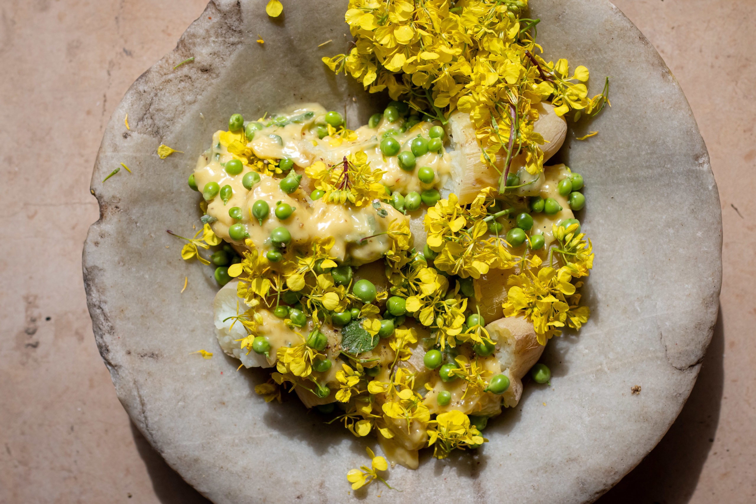 Za'atar potato salad on a ceramic plate finished with yellow flowers