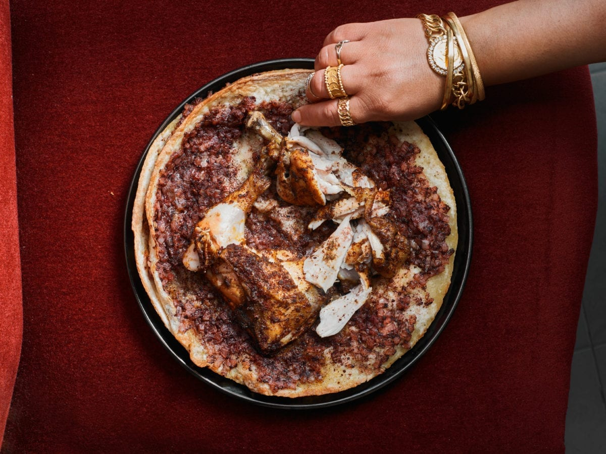 Palestinian masakhan (chicken with sumac over flatbread) on a red tablecloth