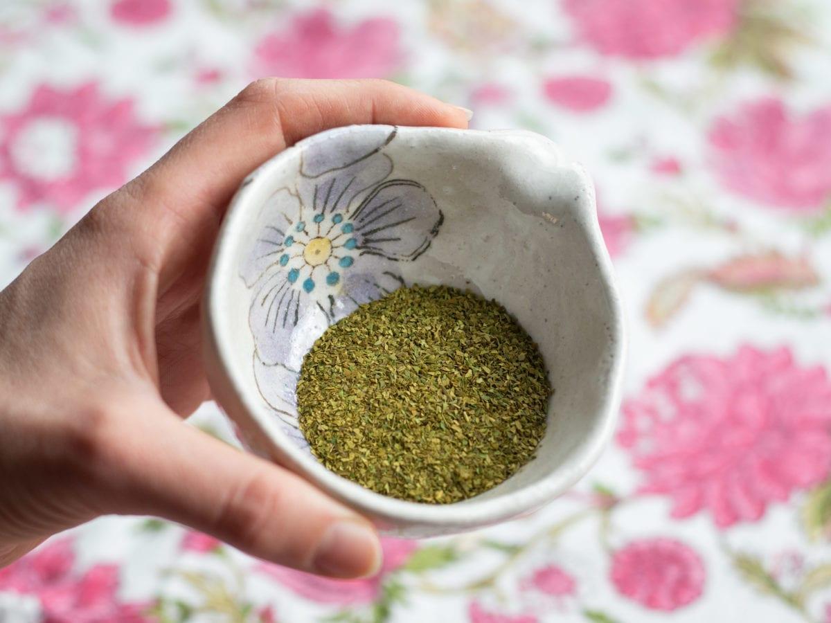 Small ceramic bowl with citrus leaf powder in it