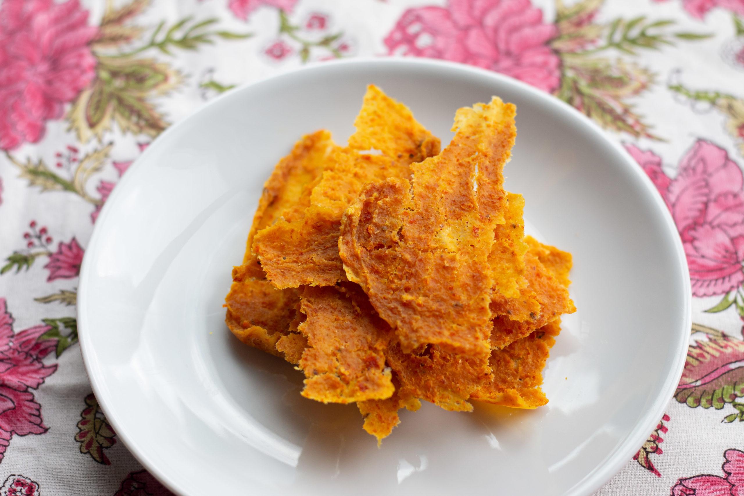 لفافة البرتقال وبذور كزبره على صحن ابيض فوق غطاء طاوله ملون