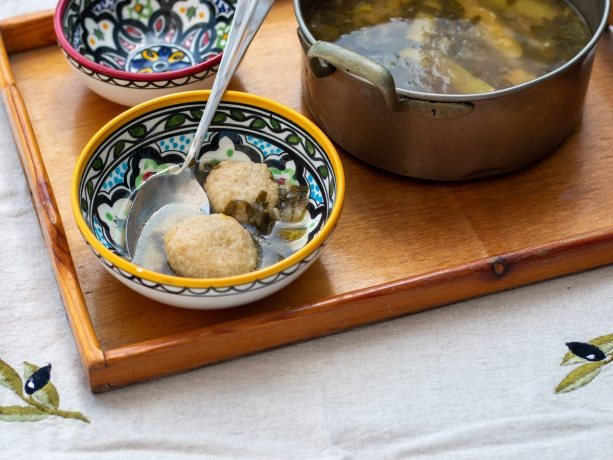 Iraqi dumpling soup called kubbeh in a pot with two ceramic bowls next to it