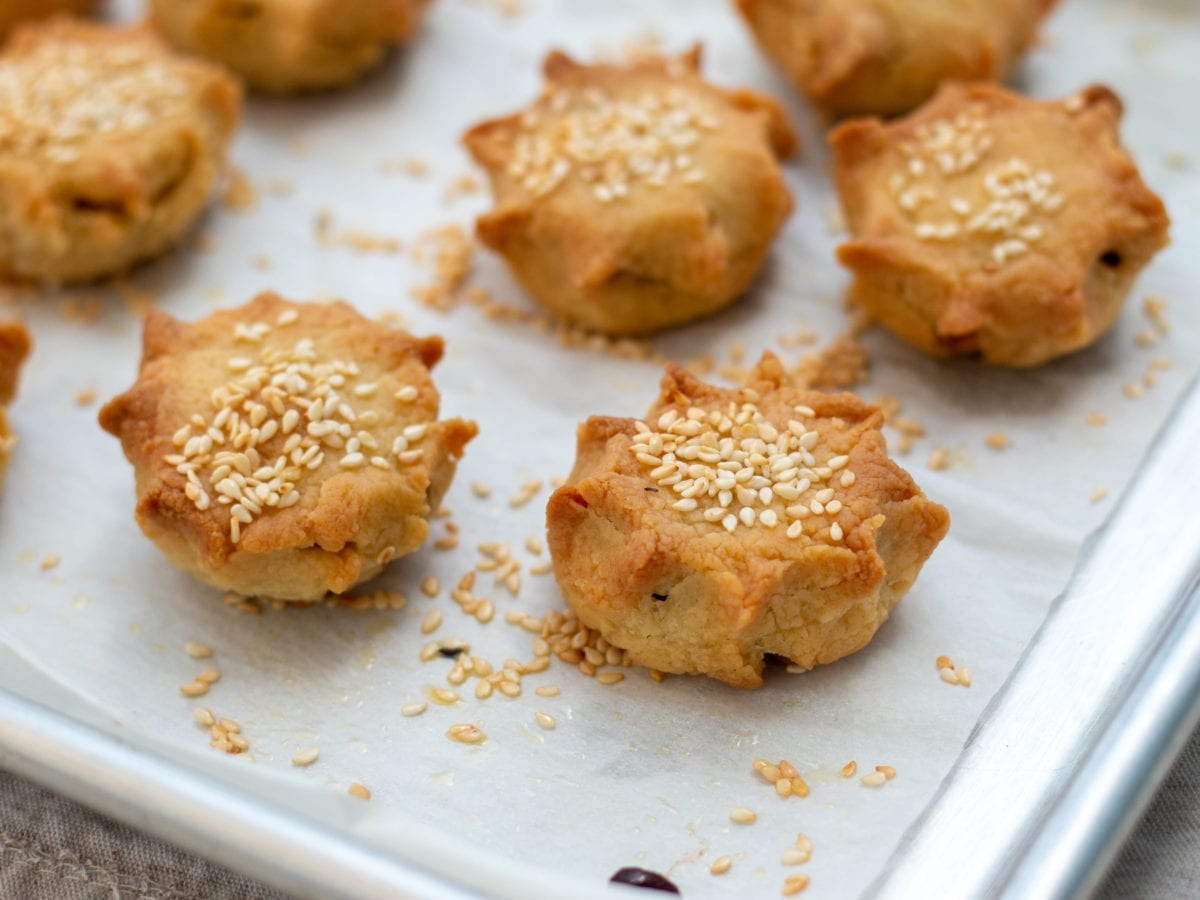 Small savory pastries called pastelicos topped with sesame seeds on a piece of parchment paper