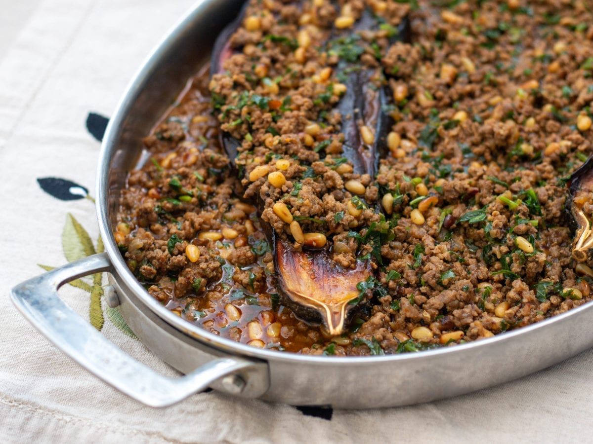 Oval casserole dish with eggplant, ground meat, pine nuts and herbs on a white tablecloth