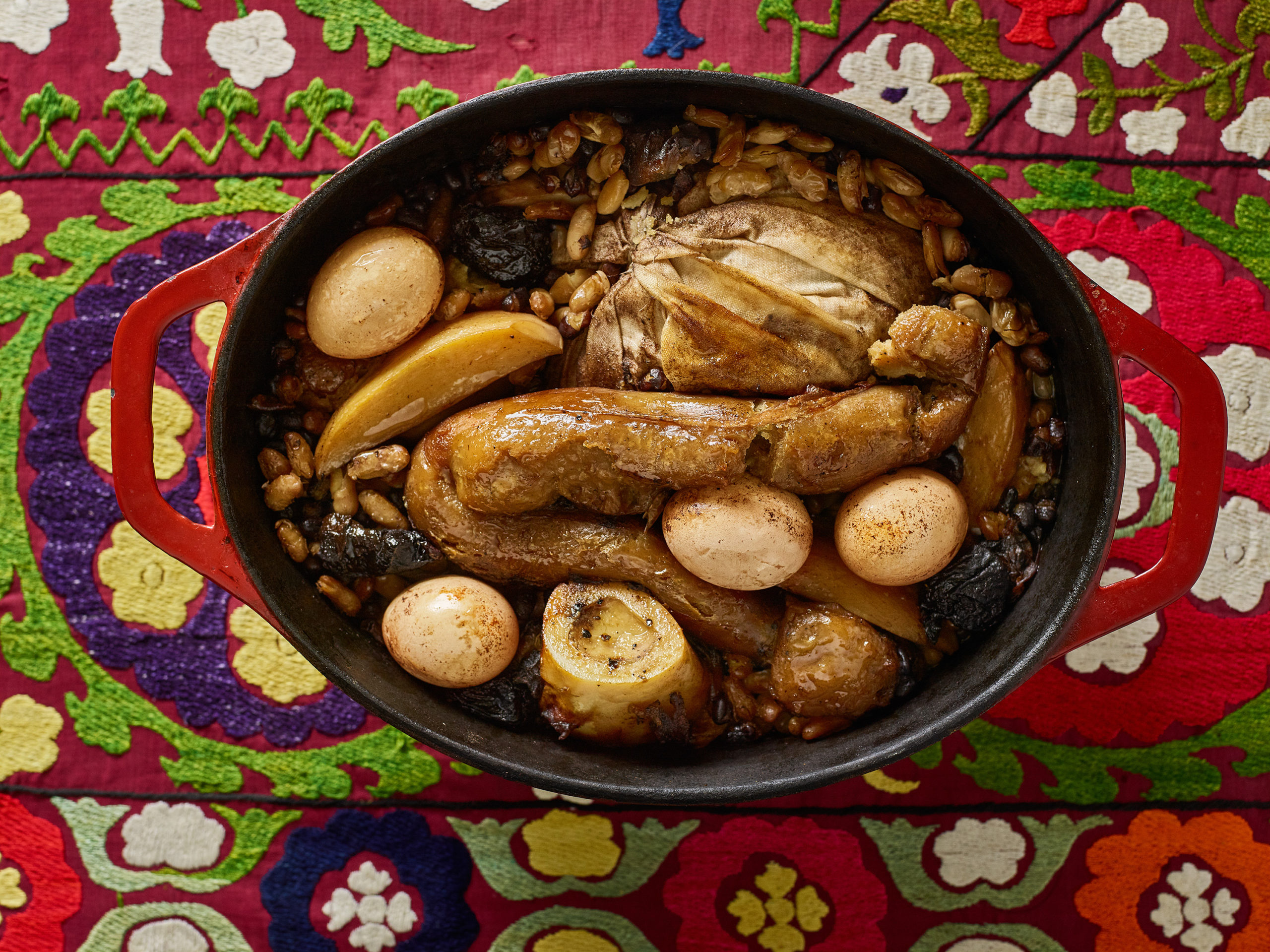 Hamin (cholent) in an oval Dutch oven with eggs, beans, and bone marrow
