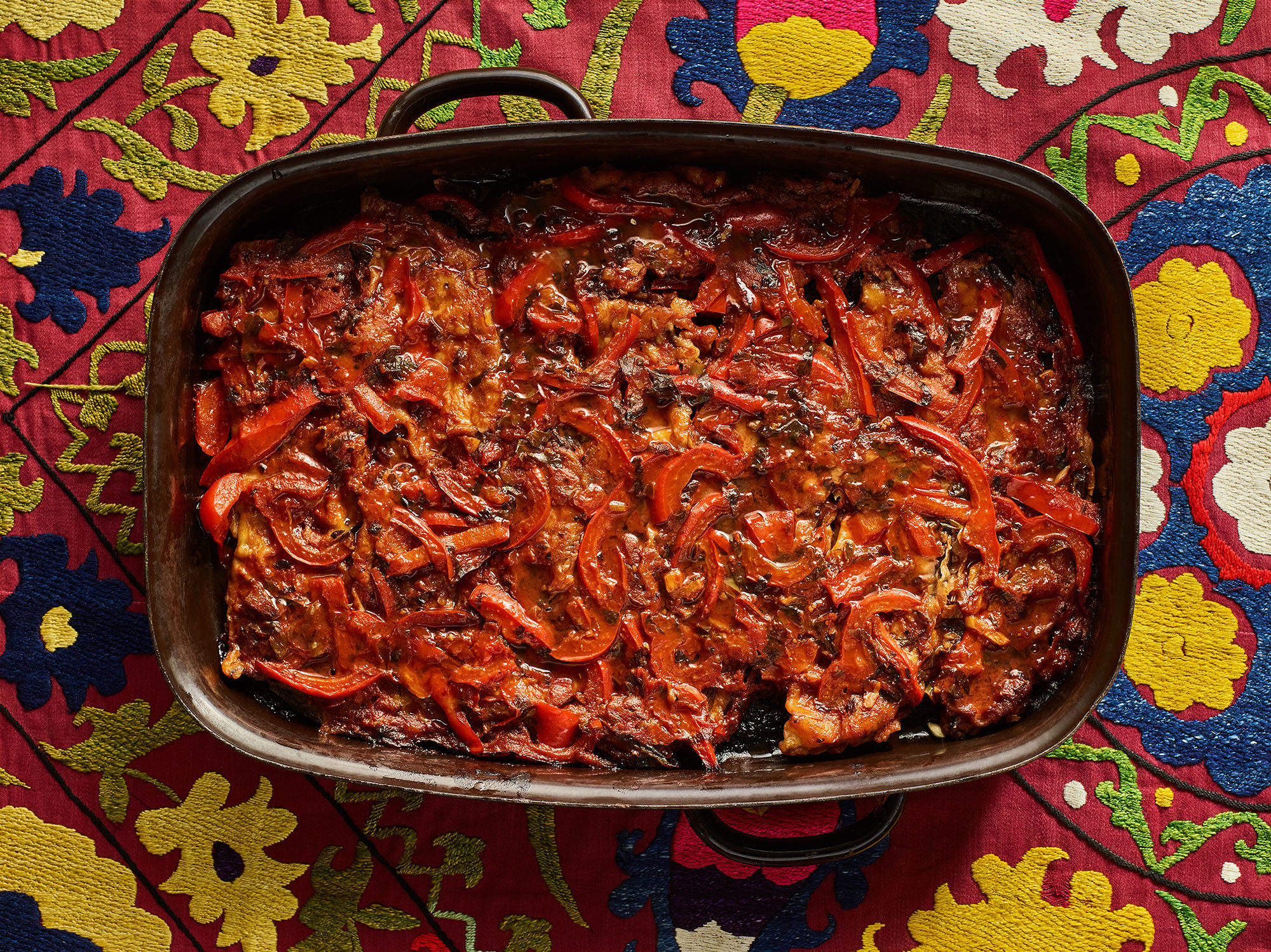 Eggplants with tomatoes and peppers in a rectangular baking dish atop a colorful tablecloth