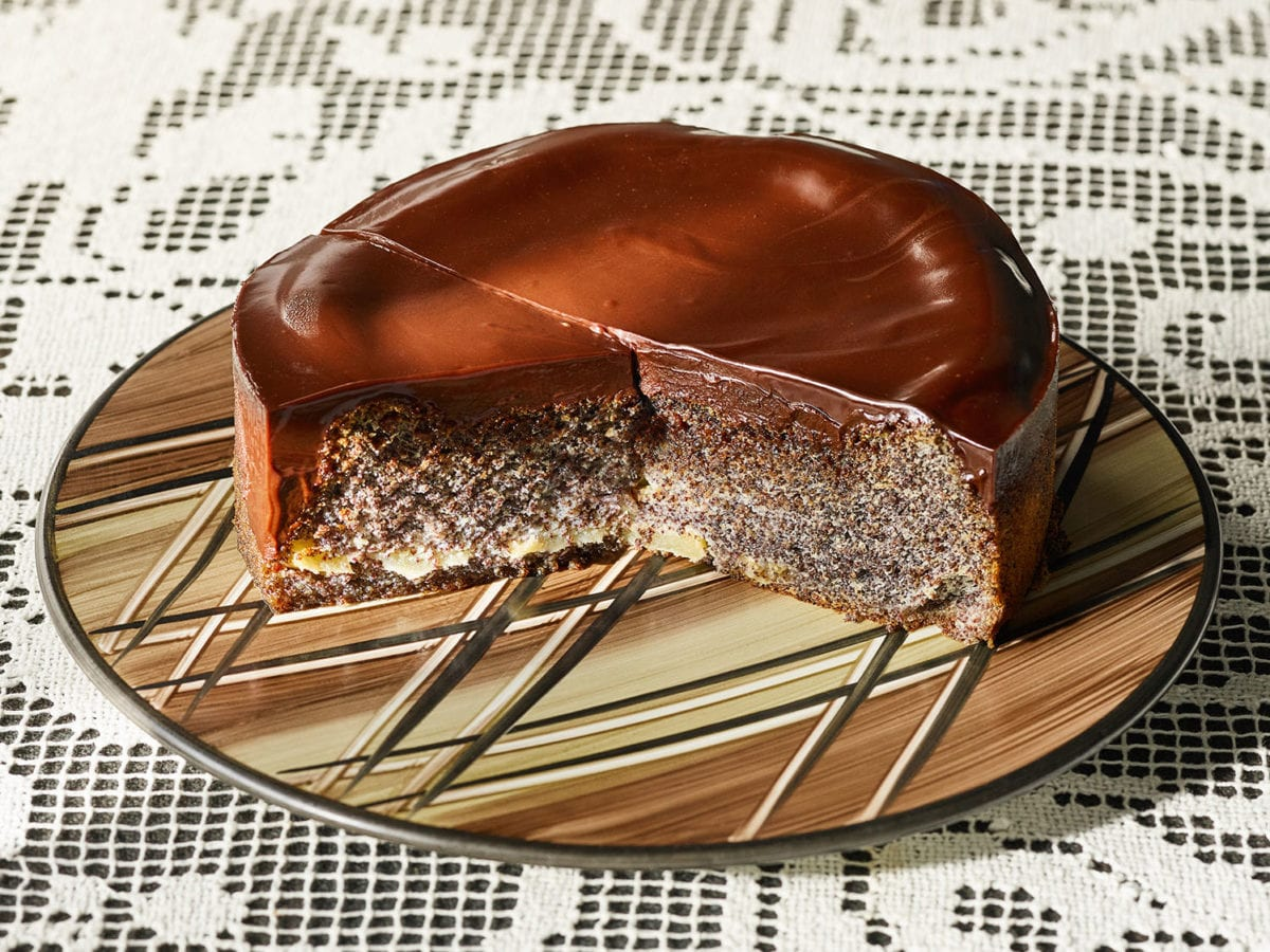 Poppyseed cake on a brown and tan platter atop a lace tablecloth