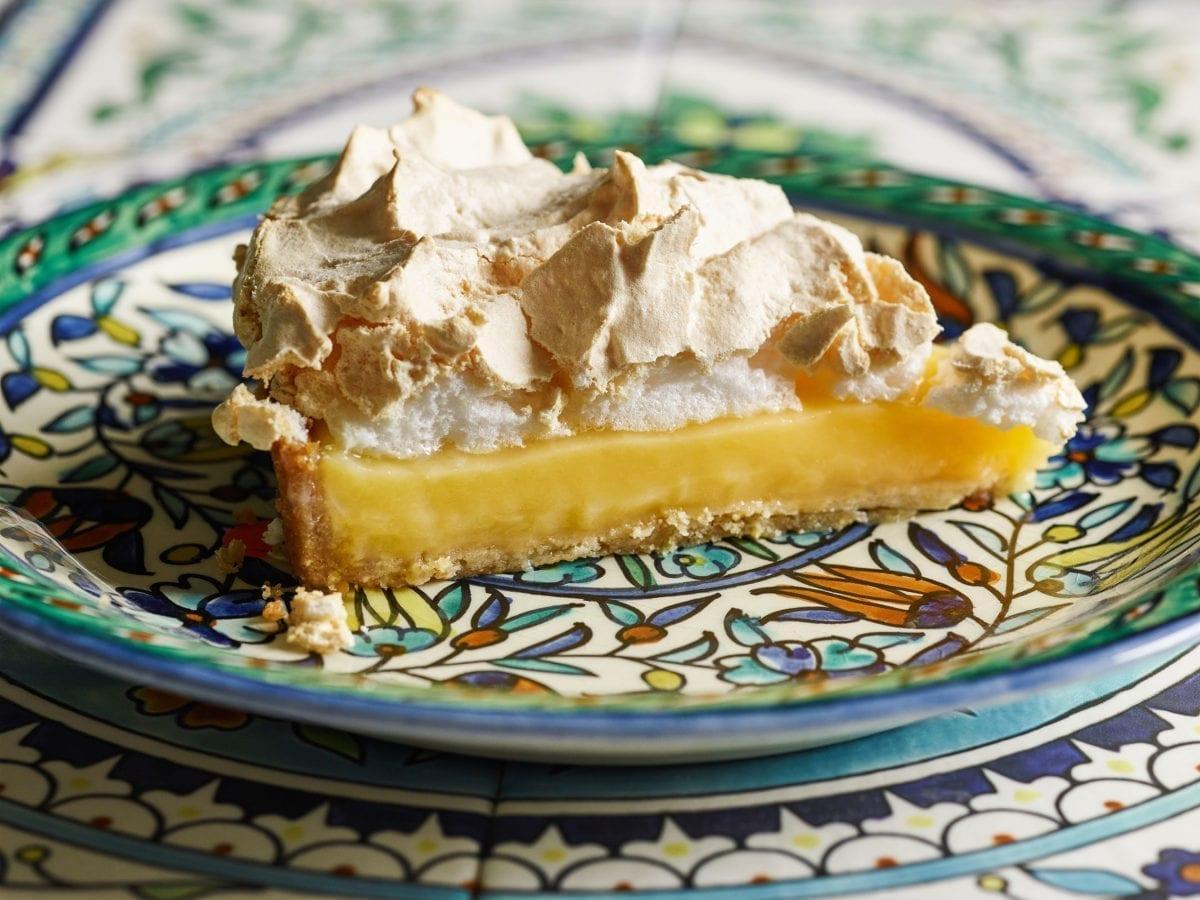 Slice of lemon meringue pie on a ceramic plate with blue detail