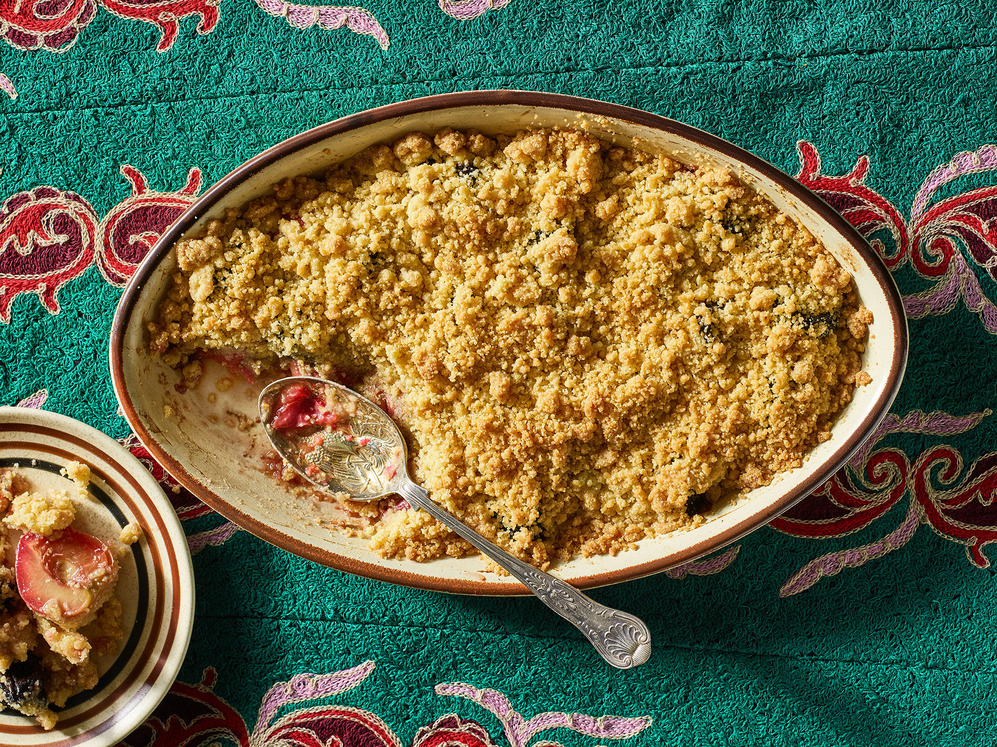Plum crumble in an oval-shaped baking dish atop a green and red tablecloth