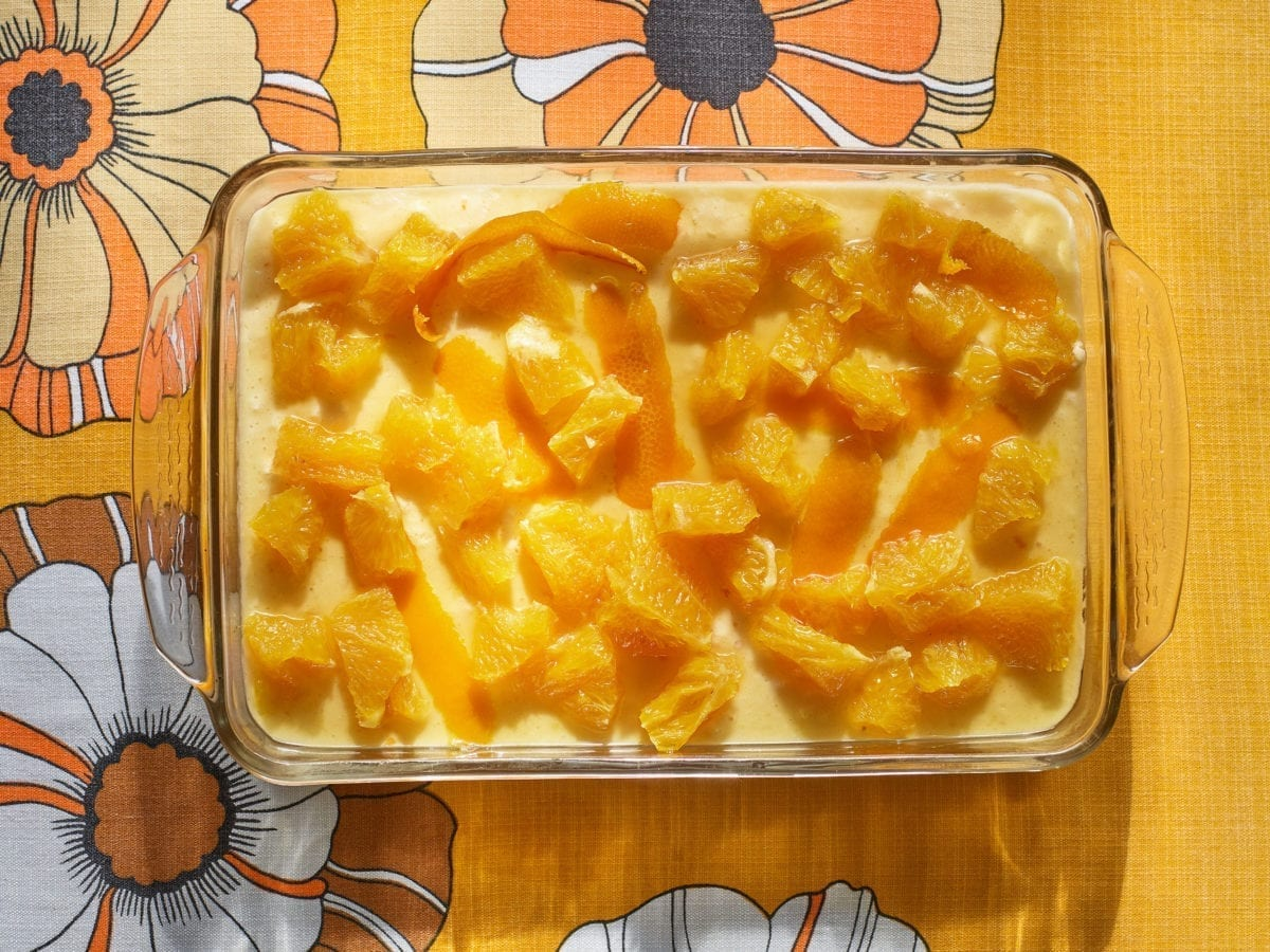 Orange bavarian dessert in a glass baking dish atop a yellow and orange tablecloth