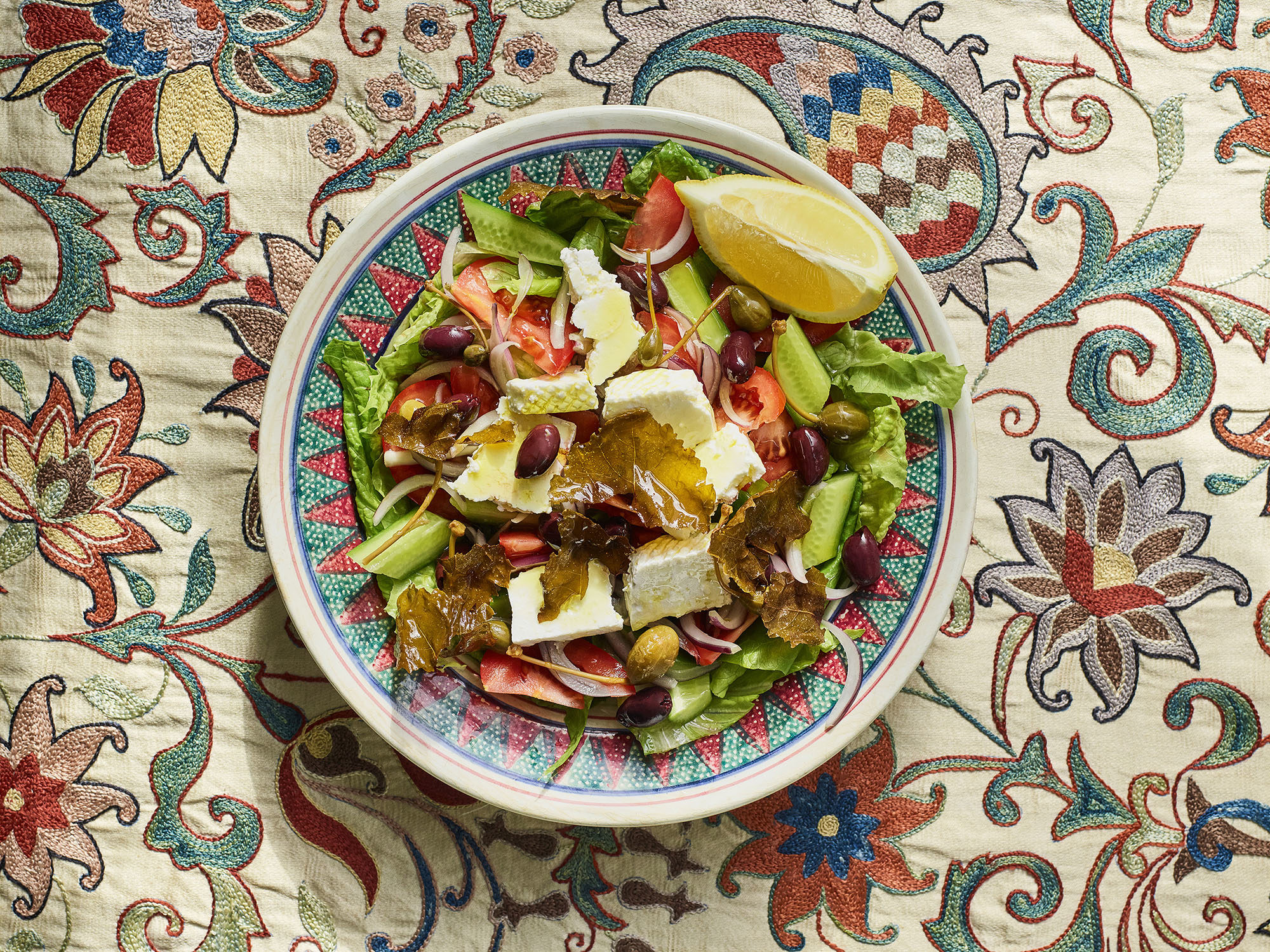 Nechama Rivlin's salad with lettuce, grape leaves, tomatoes, olives and lemon in a ceramic bowl