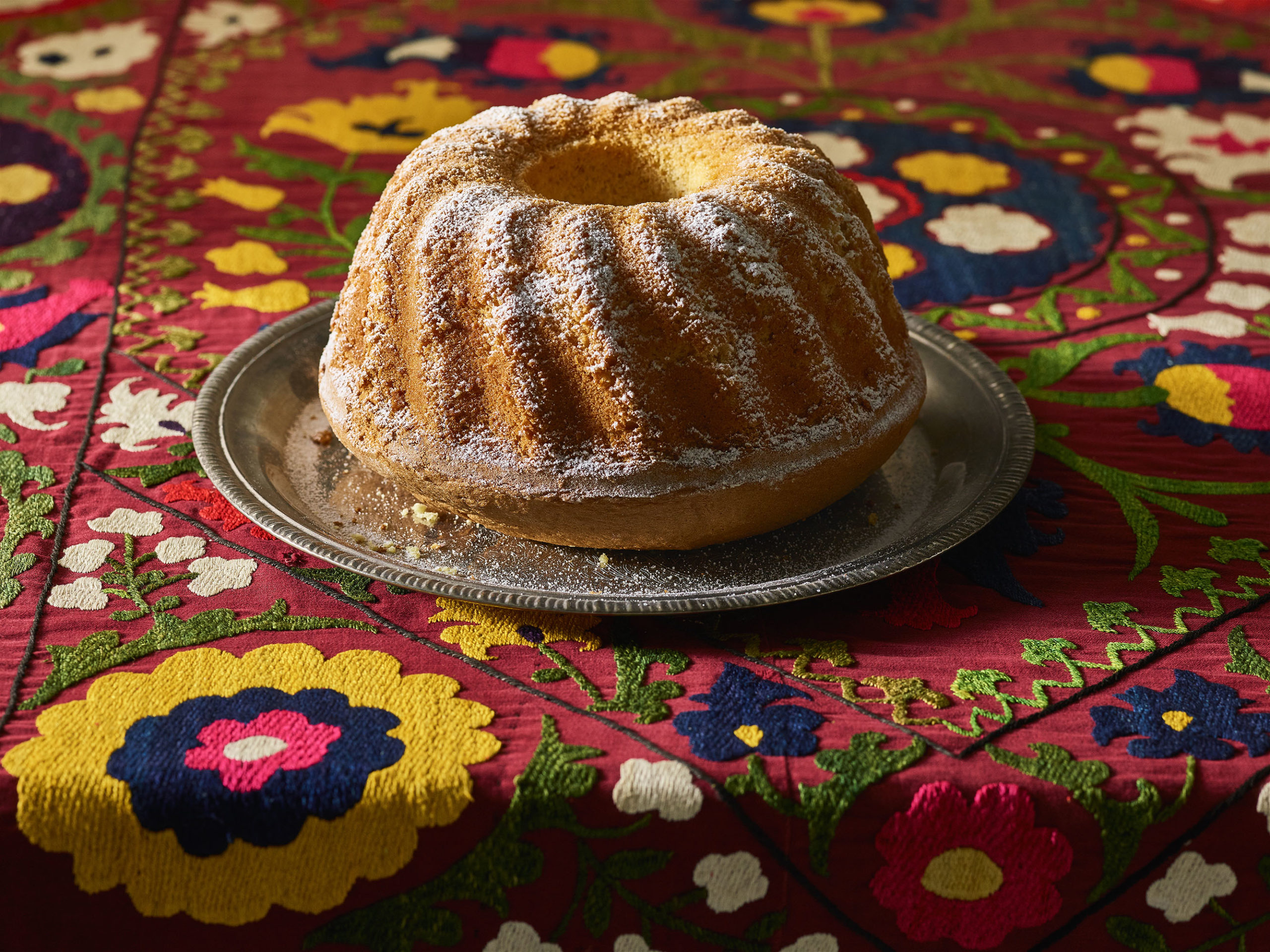 Orange juice bundt cake on a silver platter atop a colorful red tablecloth