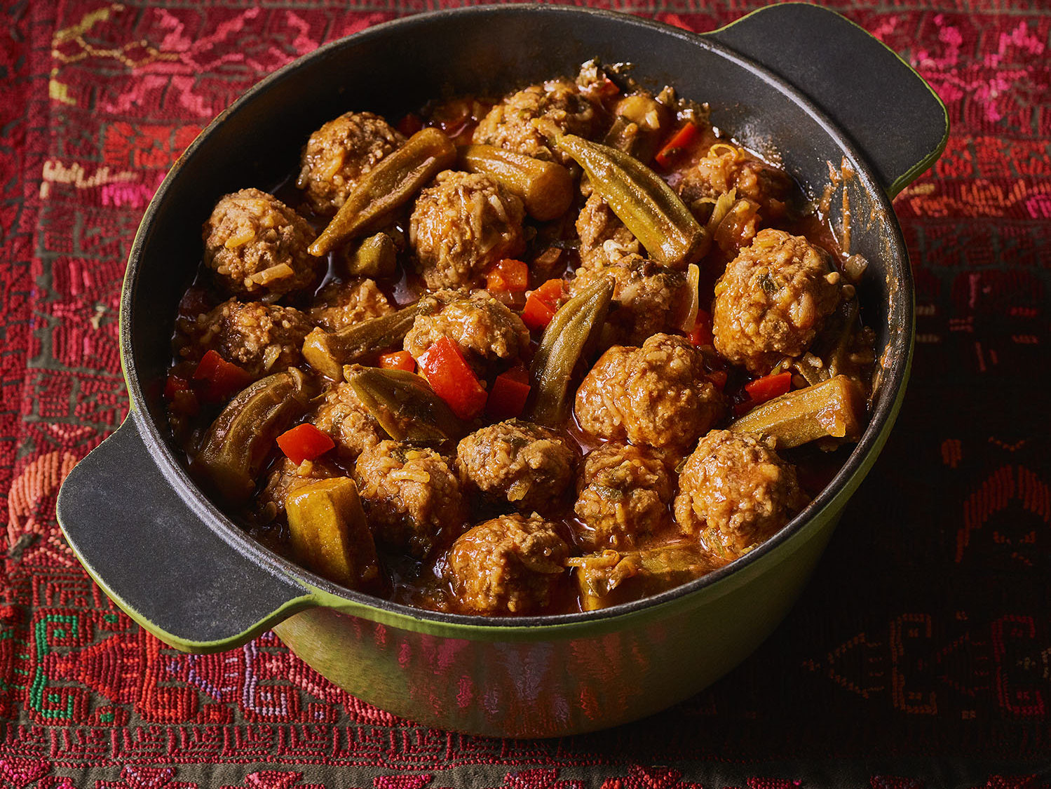 Meatballs with okra in a green Dutch oven atop a red tablecloth