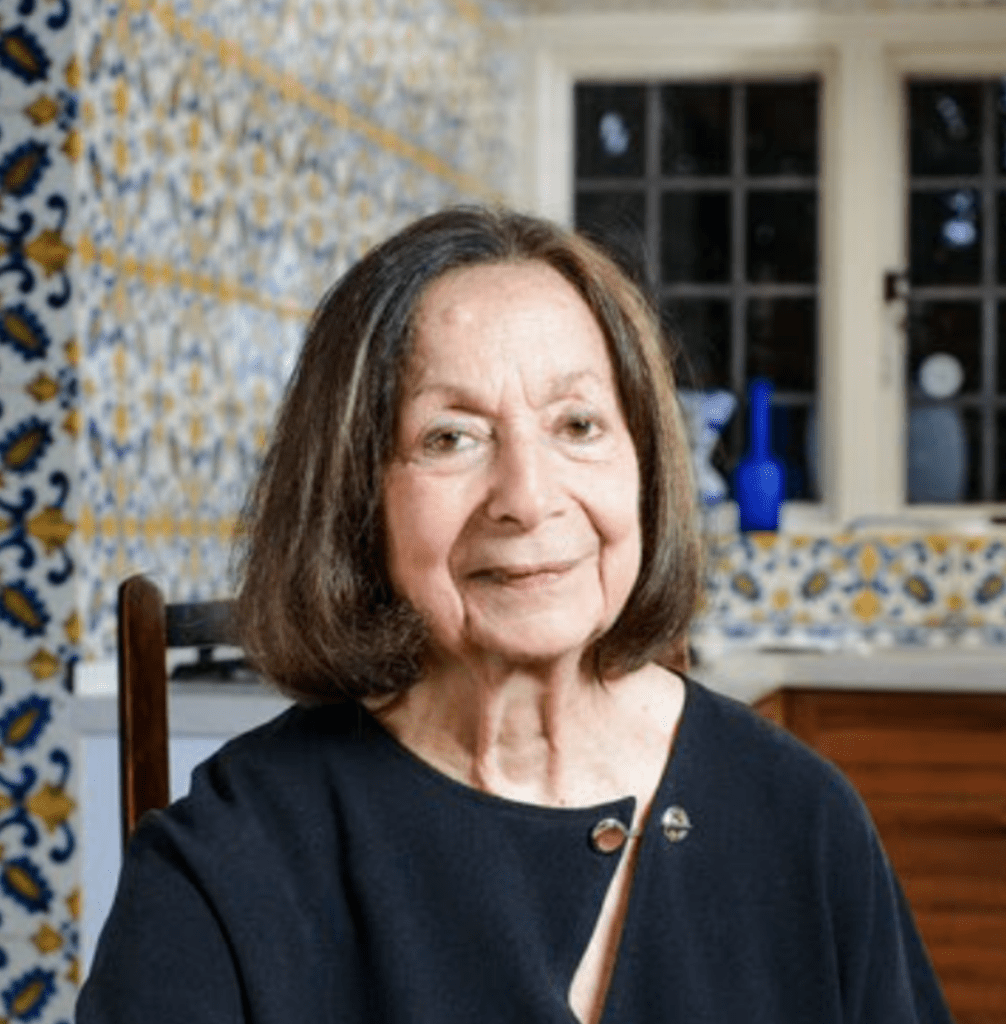 A portrait photo of Claudia Roden seated in a kitchen with bright tiles and windows behind her.