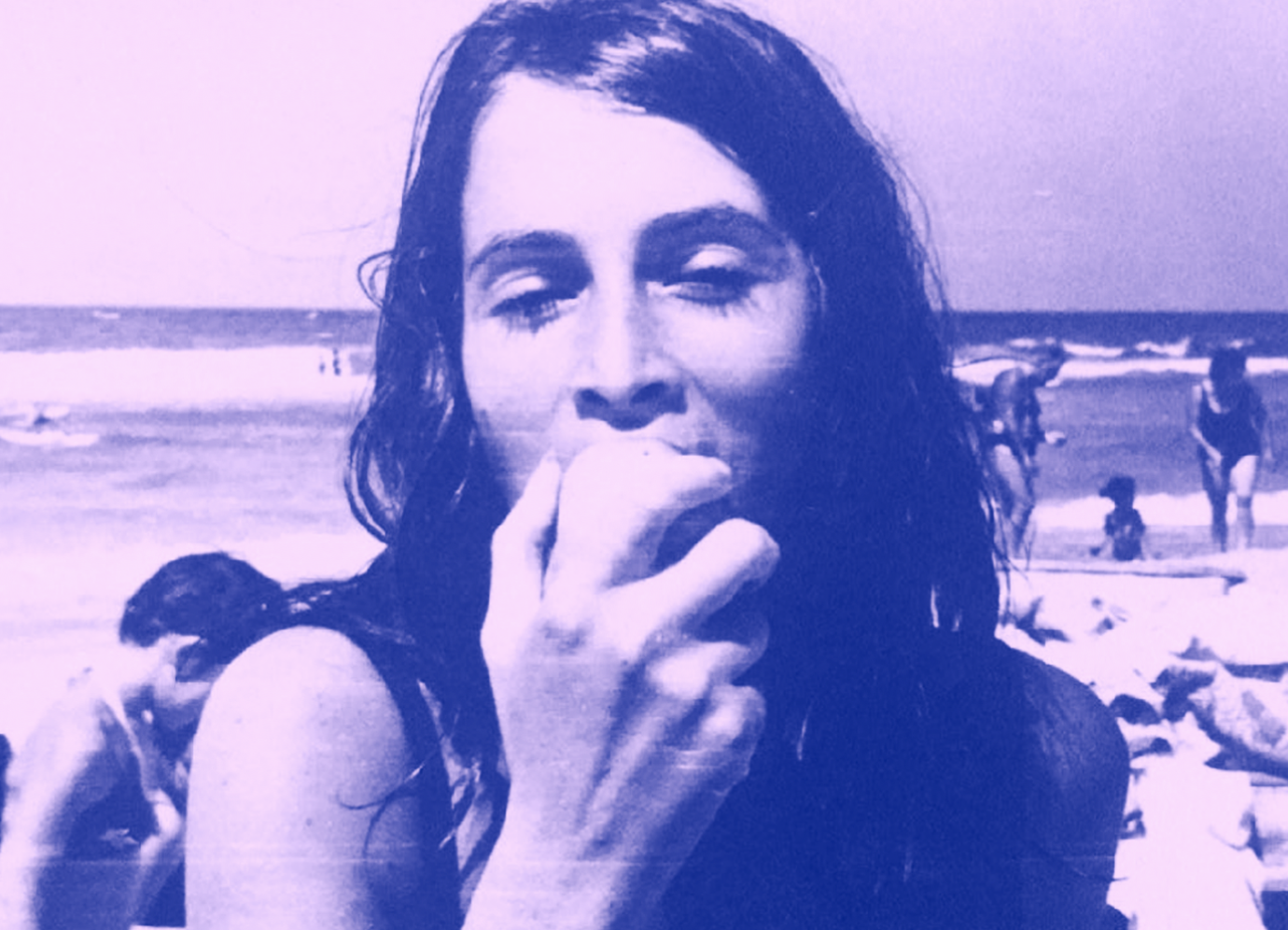 A purple / blue duotone image of Nechama Rivlin on the beach when she was in her twenties or thirties