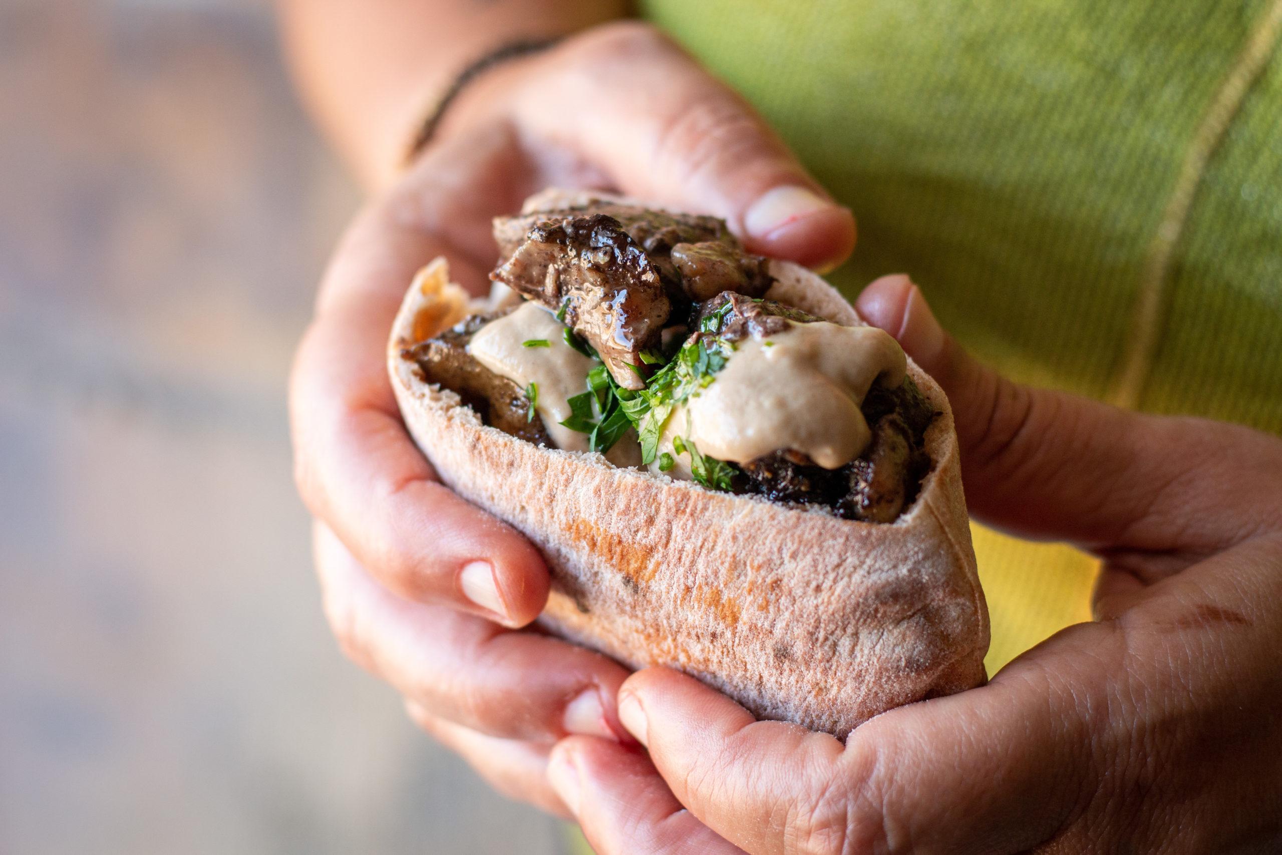 معلاق مشوي داخل خبز عربي مع طحينه تمسكه يدان