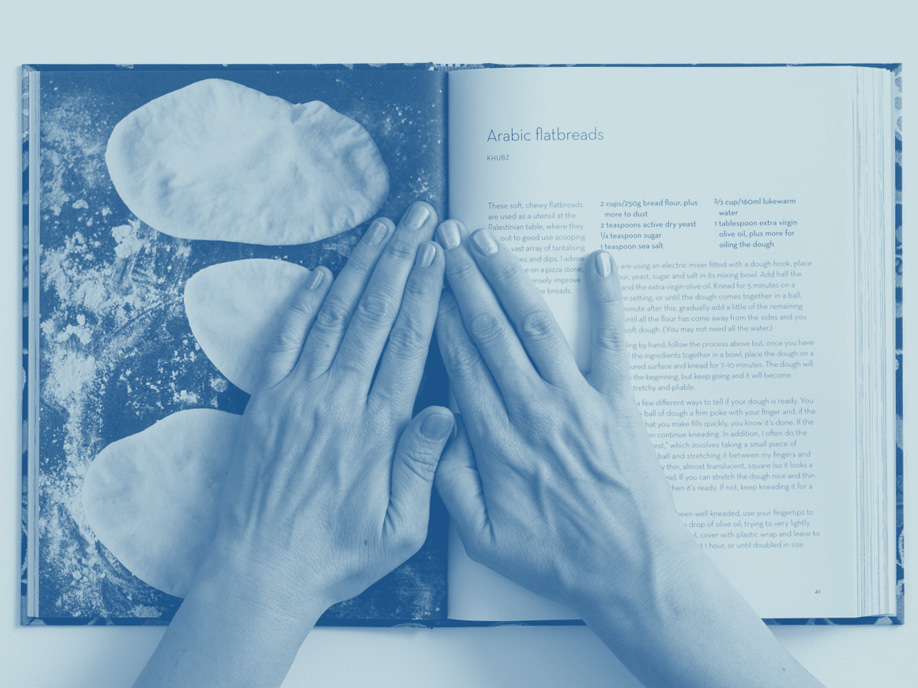 Hands atop pages from a cookbook