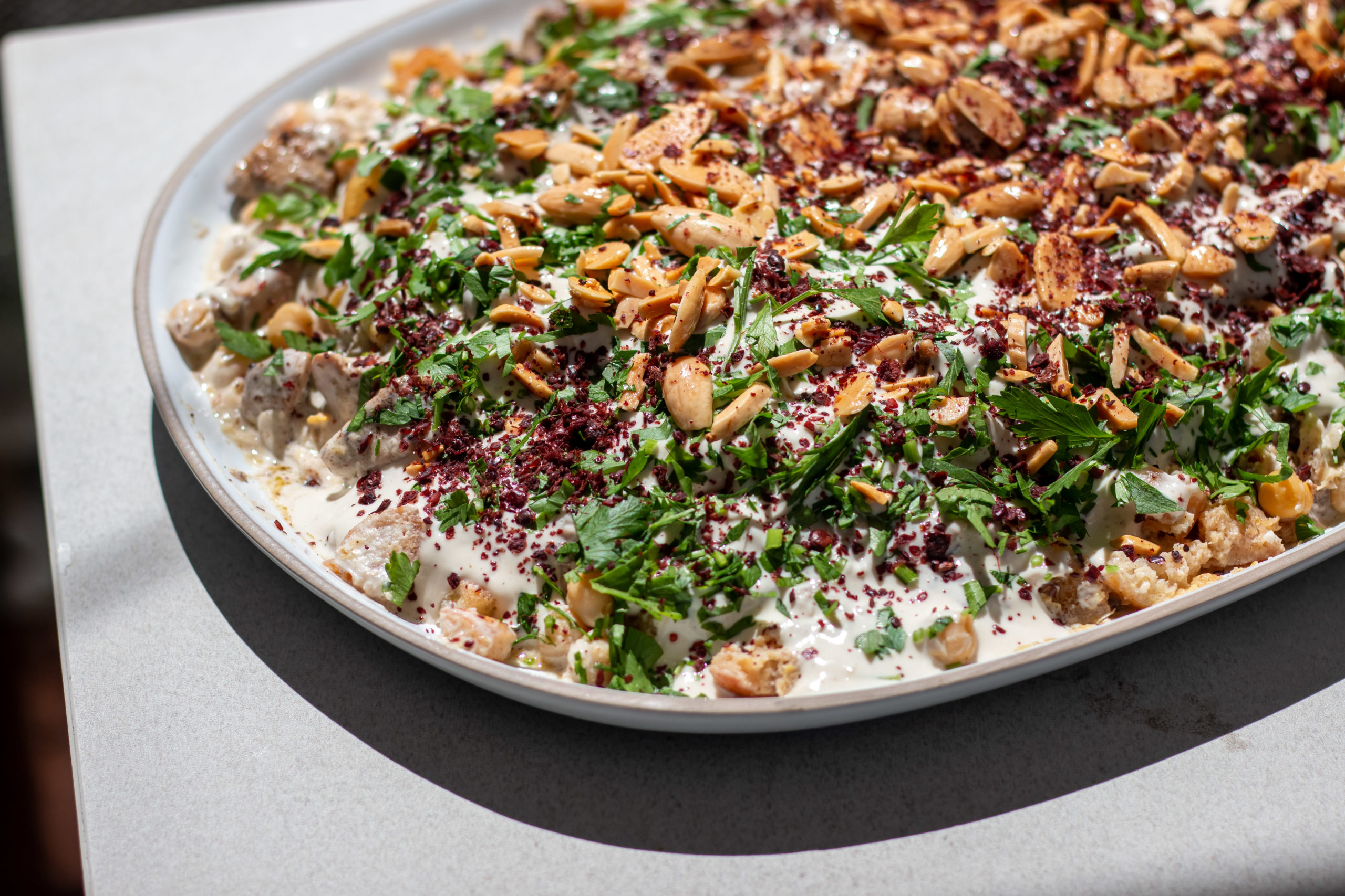 Platter of Palestinian dish chicken fatteh topped with nuts, herbs, and spices Fatte