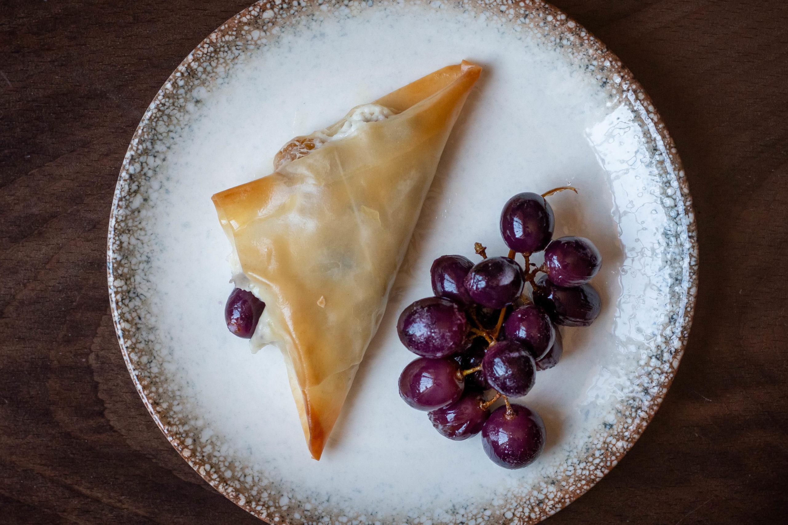 Filo triangles stuffed with kashta, grapes and raisins on white plate