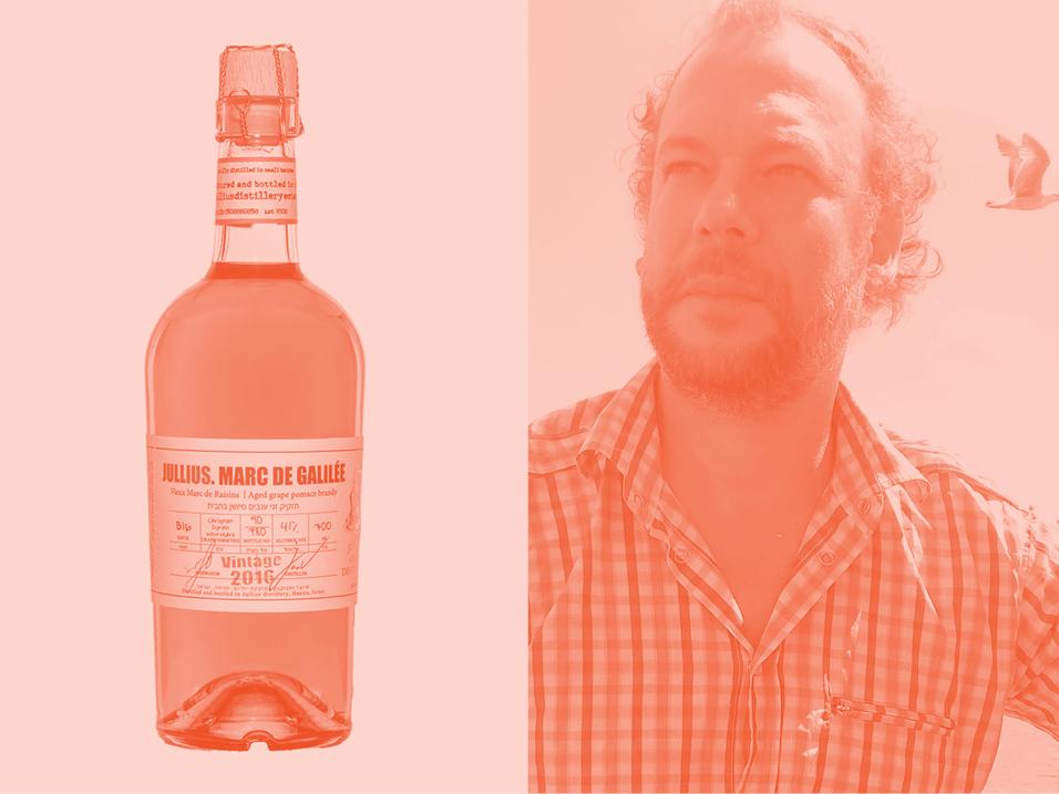 Distiller Yuval Hargil and a bottle of his Marc de Galilee liquor.