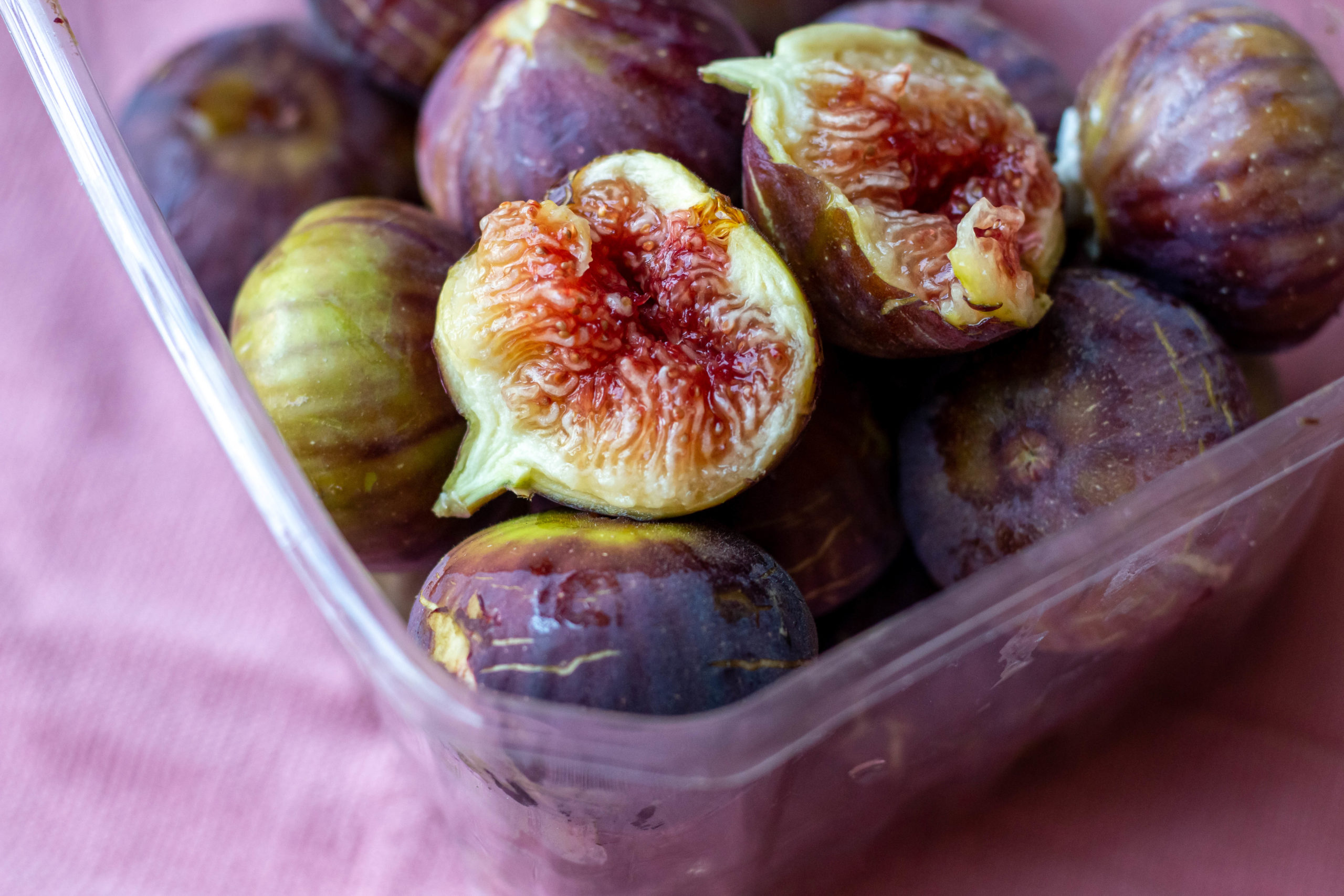 Figs in a plastic container on a purple tablecloth